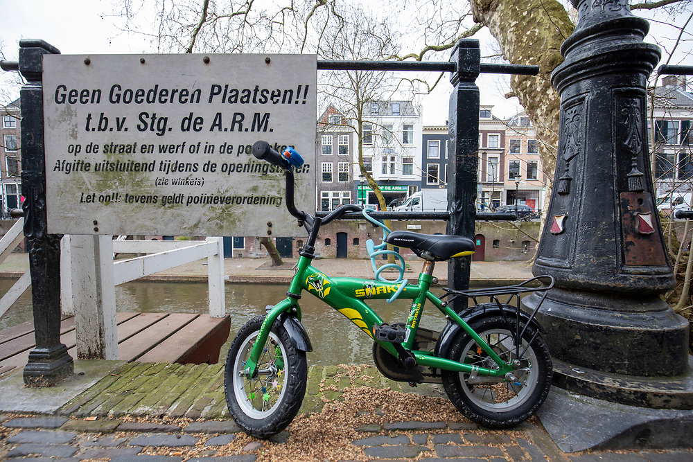 Een kinderfiets staat met een slot vast aan een hek op de Oudegracht in Utrecht.<br /> <br /> A child's bike is locked to a fence on the Oudegracht in Utrecht.