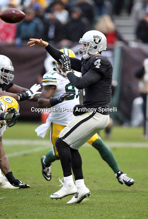 Oakland Raiders quarterback Derek Carr (4) throws a pass under pressure during the 2015 week 15 regular season NFL football game against the Green Bay Packers on Sunday, Dec. 20, 2015 in Oakland, Calif. The Packers won the game 30-20. (©Paul Anthony Spinelli)