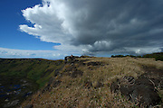 A big cloud hangs over the crater rim of Rano Kau on Easter Island, Chile