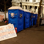 Blue portaloos and a sign saying; ' Planet 4 sale. Population 6bl. Resistnace expected.' outside St Paul's Cathedral. The camp Occupy London Stock Exchange outside St Paul's Cathedral was in the morning served with eviction notice after months of legal battle with the Corporation of London. The site was occupied Oct 15th.
