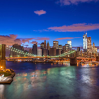 Brooklyn bridge and New York city skyline at night taken from Manhattan bridge
