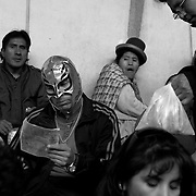 Wrestling fans wait patiently before the bouts at the El Alto Multifunctional Centre, Bolivia where the  'Titans of the Ring' wrestling group who perform each Sunday.  The wrestling group includes the fighting Cholitas, a group of Indigenous Female Lucha Libra wrestlers who fight the men as well as each other for just a few dollars appearance money. El Alto, Bolivia, 24th January 2010. Photo Tim Clayton