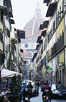 View of church dome from crowded narrow street Florence Italy