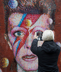© Licensed to London News Pictures. 10/01/2017. London, UK. A fan takes a photograph of a mural and shrine to David Bowie in Brixton on the first anniversary of his death. David Bowie was born in Brixton, south London. Photo credit: Peter Macdiarmid/LNP