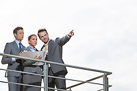 Businessman showing something to coworkers on terrace against sky