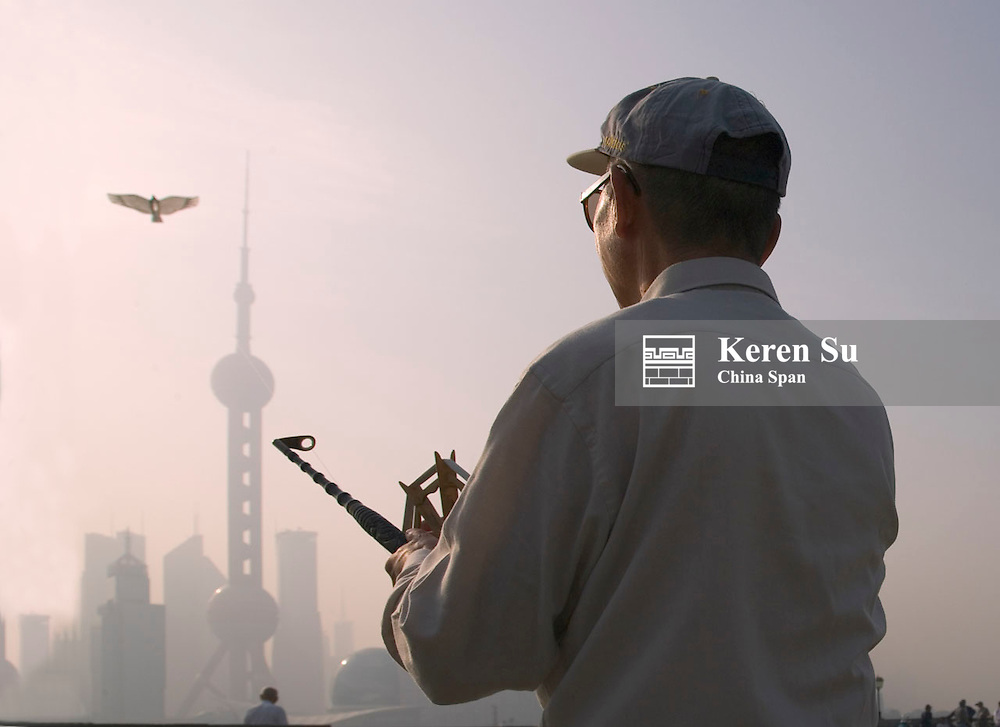 Man flying kite on the Bund, Pudong skyline in the distance, Shanghai, China