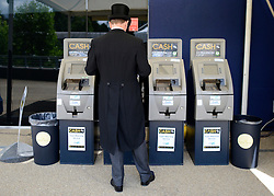 © Licensed to London News Pictures. 19/06/2012. Ascot, UK  A man uses a cash machine. Day one at Royal Ascot 19 June 2012. Royal Ascot has established itself as a national institution and the centrepiece of the British social calendar as well as being a stage for the best racehorses in the world.. Photo credit : Stephen Simpson/LNP