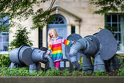 © Licensed to London News Pictures. 05/07/2019. Settle UK. 4 Year old Scarlet plays with two Elephant's made entirely out of flowerpots at the 14th Settle Flowerpot festival in the Yorkshire Dales which takes place in the town throughout July & August. Photo credit: Andrew McCaren/LNP