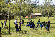 The team of volunteers playing an energising game called 'stuck in the poo' for their school training session with pupils at Endagikot school as part of the ICS Raleigh SWASH (school water, sanitation and hygiene plan) project. Mbulu, Manyara district, Tanzania. Working in partnership with the Diocese of Mbulu Development Department (DMDD); part of Caritas Tanzania.