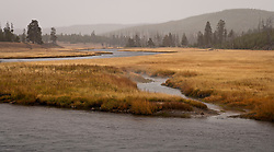 A geothermal hotspring surfaces and flows into the Madison River in Yellowstone National Park, Wyoming, USA