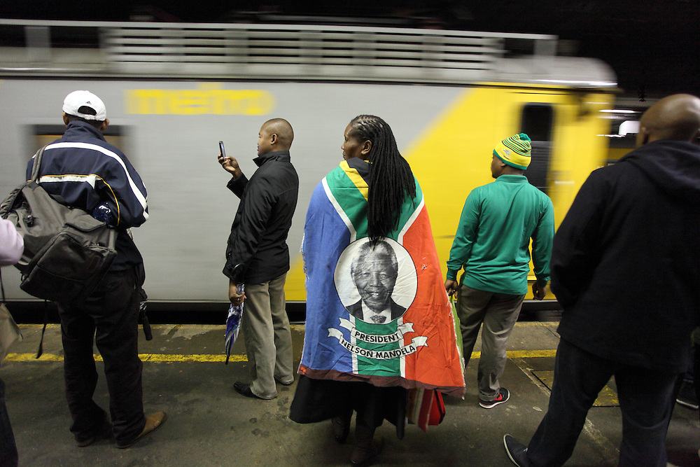 Mourners travel by train to the official memorial service for Nelson Rolihlahla Mandela the FNB stadium in Soweto near Johannesburg. South Africa.<br />