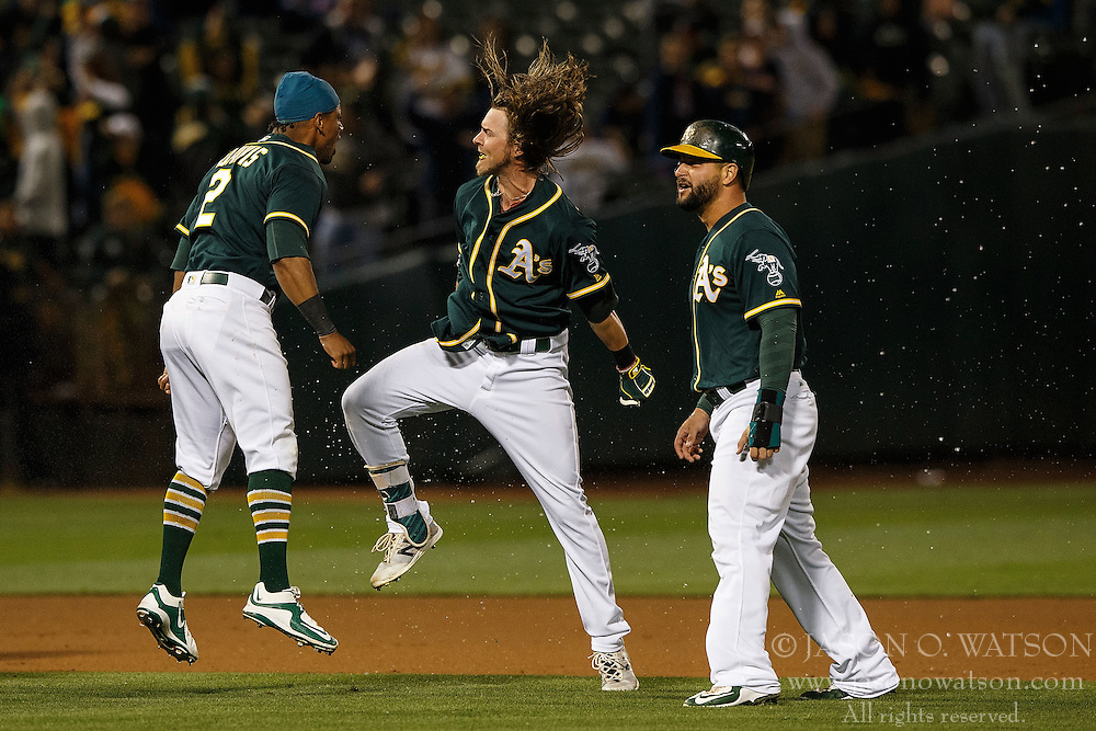 OAKLAND, CA - JULY 19:  Josh Reddick #22 of the Oakland Athletics is congratulated by Khris Davis #2 and Yonder Alonso #17 after hitting a walk off single against the Houston Astros after the game against the Houston Astros at the Oakland Coliseum on July 19, 2016 in Oakland, California. The Oakland Athletics defeated the Houston Astros 4-3 in 10 innings.  (Photo by Jason O. Watson/Getty Images) *** Local Caption *** Josh Reddick; Khris Davis; Yonder Alonso