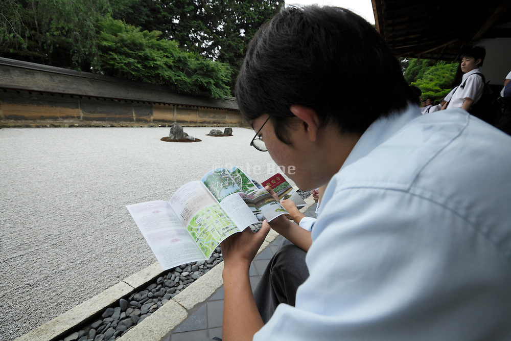 Japanese student reading the folder at the Ryoanji temple zen stone garden in Kyoto