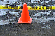 red cones and yellow tape to protect people from walking on an iced over path
