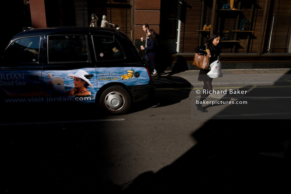 A Jordan holiday advert on the side of a London taxi cab and a busy career woman who crosses the road behind.