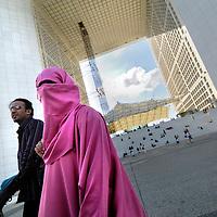 FRANCE, Paris. Muslim couple by the Grade Arche of La Defence.