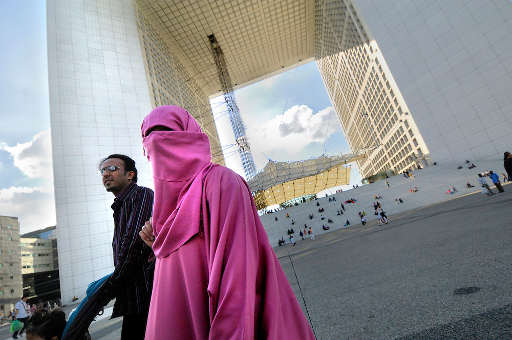 FRANCE, Paris. Muslim couple by the Grade Arche of La Defence.
