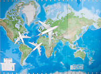 Model airplanes flying in different direction over world map