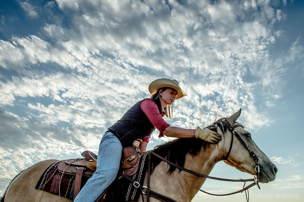 Bird Researcher Marisa Lipsey brings her horses back after working on a cattle drive at the Matador ranch &quot;grass bank&quot;. The &ldquo;grass bank&quot; is an innovative way to leverage conservation gains, in which ranchers can graze their cattle at discounted rates on Conservancy land in exchange for improving conservation practices on their own &ldquo;home&rdquo; ranches. In 2002, the <br /> Conservancy began leasing parts of the ranch to neighboring ranchers who were suffering from  severe drought, offering the Matador&rsquo;s grass to neighboring ranches in exchange for their  participation in conservation efforts. The grassbank has helped keep ranchers from plowing up native grassland to farm it; helped remove obstacles to pronghorn antelope migration; improved habitat for the Greater Sage-Grouse and reduced the risk of Sage-Grouse colliding with fences; preserved prairie dog towns and prevented the spread of noxious weeds. (Photo By Ami Vitale)