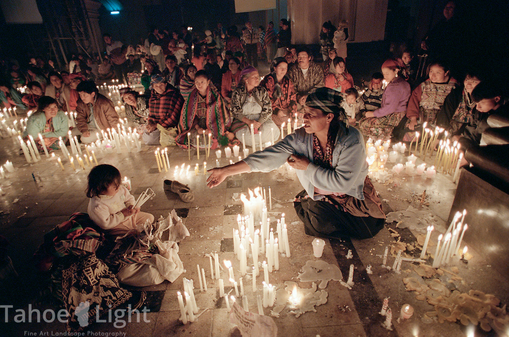 A Mayan woman with her child plants candles inside the Black Christ Basilica in the Guatemalan town of Esquipulas.