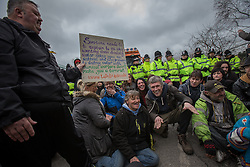 © Licensed to London News Pictures . 17/03/2014 . Barton Moss , Salford , UK . Protesters , including Bez (doing his freaky dance move ), sit in the road , blocking the lorries' path . Happy Mondays dancer , Bez ( Mark Berry ) , joins protesters at the Barton Moss anti-fracking protest site in Salford today (Monday 17th March 2014) . Bez has said he will stand for MP in the constituency of Salford and Eccles in 2015 . Photo credit : Joel Goodman/LNP