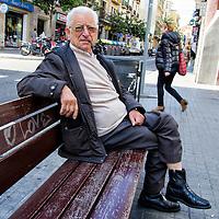 Un hombre mayor descansa, fumando su pipa en la calle Gran de Gracia (Gran de Gràcia) en Barcelona, España. An older man sits, smoking his pipe in Gran de Gracia (Gran de Gràcia) street in Barcelona, Spain.
