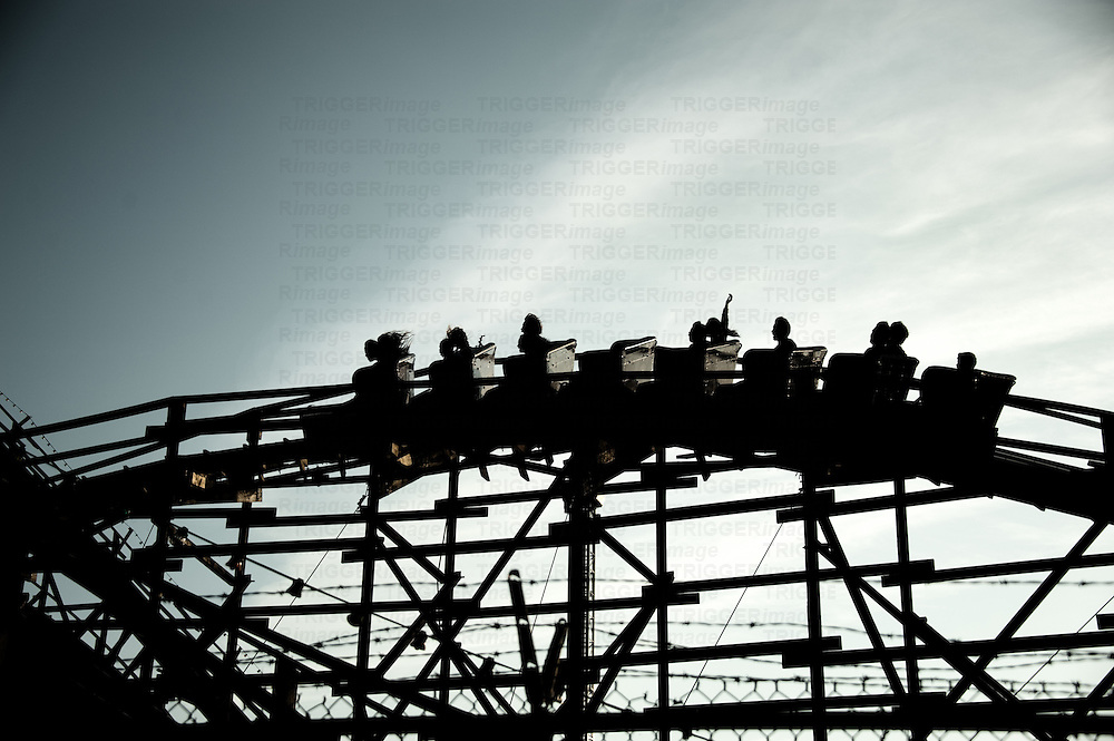A silhouetted roller coaster car on an old wooden track as riders ride in the early evening.