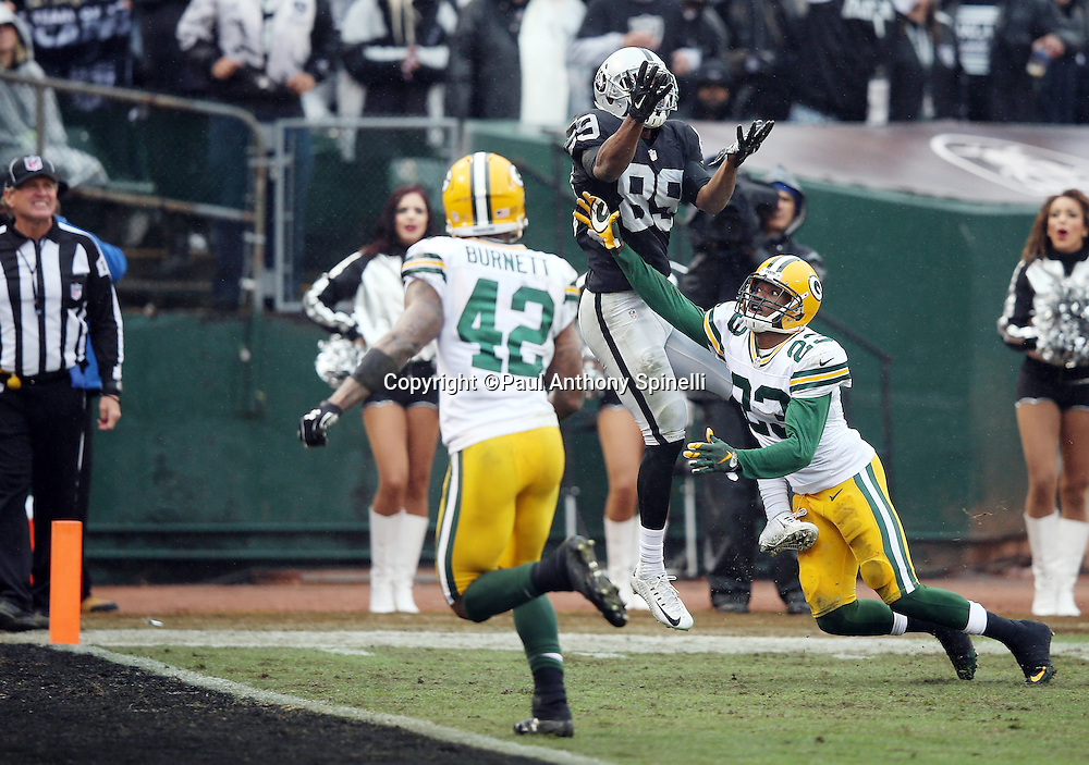 Green Bay Packers strong safety Morgan Burnett (42) looks on as Oakland Raiders wide receiver Amari Cooper (89) leaps and catches a 26 yard third quarter touchdown pass that gives the Raiders a 20-17 lead while covered by Green Bay Packers rookie cornerback Damarious Randall (23) during the 2015 week 15 regular season NFL football game against the Green Bay Packers on Sunday, Dec. 20, 2015 in Oakland, Calif. The Packers won the game 30-20. (©Paul Anthony Spinelli)