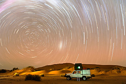 Star trails encircle a tourist vehicle camping in sand dunes in the southern hemisphere of Namibia's Skeleton Coast, Skeleton Coast, Namibia
