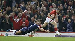 Wales' Gareth Davies evades a tackle from Scotland's Chris Harris to score his sides opening try of the game during the NatWest 6 Nations match at the Principality Stadium, Cardiff.