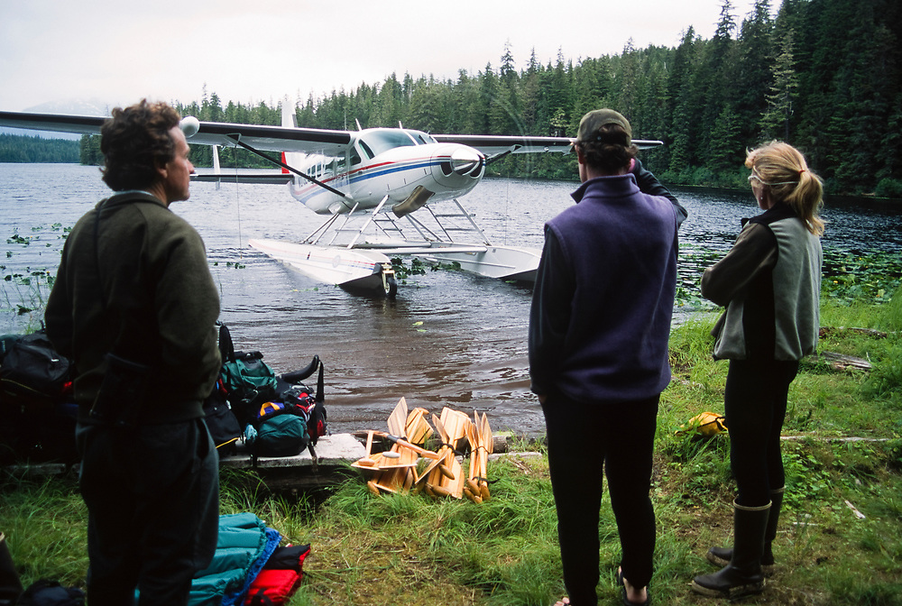 Alaska. Mole Harbor, Cross Admirality Canoe Route. Three canoers are greeted by their float plane pick up.
