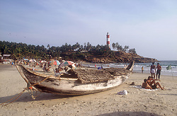Fishing boat and tourists on the beach at Kovalam beach; Kerala; India,