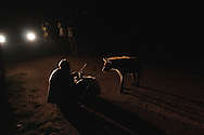 One of the Hyena Men of Harar, Ethiopia, tempts a hyena with camel meat under the illumination of car headlights. While the feedings like this have only taken place for roughly 40 years, the tradition of interacting with hyenas in some form has existed for over 700 years.
