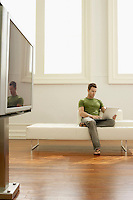 Man using laptop on sofa in modern apartment