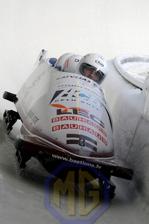 28 February 2007:    The Latvia 1 bobsled driven by Janis Minins with sidepushers Daumants Dreiskens and Oskars Melbardis, and brakeman Intars Dambis goes through turn 19 in the 1st run at the 4-Man World Championships competition on February 27 at the Olympic Sports Complex in Lake Placid, NY.