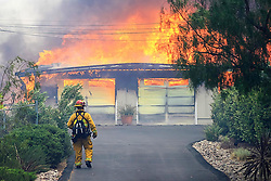 July 6, 2018 - Alpine, California, U.S. - A firefighter approaches a burning home along Olive View Road on Friday during a fire in Alpine amid a dangerous heat wave. A fast-moving brush fire in Alpine burned 400 acres, destroyed several structures and prompted evacuations. (Credit Image: © Eduardo Contreras/San Diego Union-Tribune via ZUMA Wire)
