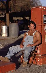 hot gas station attendant leaning on a gas pump