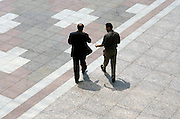 two business men walking on courtyard