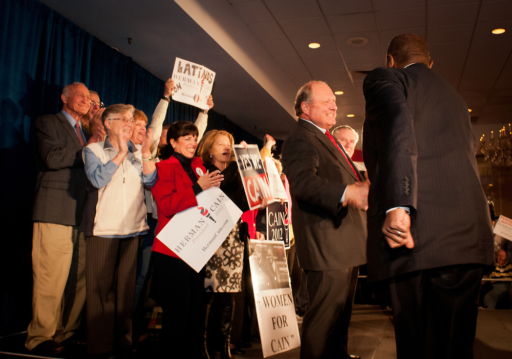 Presidential hopeful Herman Cain is greeted by supporters as he takes the stage during a campaign Rally in the Radisson Hotel in Nashua, NH.