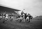 W J McBride of Ireland, jumps for the ball from a line out, with KF Gray from New Zealand, third from the right, disputing possession, ..Irish Rugby Football Union, Ireland v New Zealand, Tour Match, Landsdowne Road, Dublin, Ireland, Saturday 7th December, 1963,.7.12.1963, 12.7.1963,..Referee- H Keenen, Rugby Football Union, ..Score- Ireland 5 - 6 New Zealand, ..Irish Team, ..T J Kiernan, Wearing number 15 Irish jersey, Full Back, Cork Constitution Rugby Football Club, Cork, Ireland,..J Fortune, Wearing number 14 Irish jersey, Right Wing, Clontarf Rugby Football Club, Dublin, Ireland,..P J Casey, Wearing number 13 Irish jersey, Right Centre, University College Dublin Rugby Football Club, Dublin, Ireland, ..J C Walsh,  Wearing number 12 Irish jersey, Left Centre, University college Cork Football Club, Cork, Ireland,..A T A Duggan, Wearing number 11 Irish jersey, Left Wing, Landsdowne Rugby Football Club, Dublin, Ireland,..M A English, Wearing number 10 Irish jersey, Stand Off, Landsdowne Rugby Football Club, Dublin, Ireland, ..J C Kelly, Wearing number 9 Irish jersey, Captain of the Irish team, Scrum Half, University College Dublin Rugby Football Club, Dublin, Ireland,..P J Dwyer, Wearing number 1 Irish jersey, Forward, University College Dublin Rugby Football Club, Dublin, Ireland, ..A R Dawson, Wearing number 2 Irish jersey, Forward, Wanderers Rugby Football Club, Dublin, Ireland, ..R J McLoughlin, Wearing number 3 Irish jersey, Forward, Gosforth Rugby Football Club, Newcastle, England, ..W J McBride, Wearing number 4 Irish jersey, Forward, Ballymena Rugby Football Club, Antrim, Northern Ireland,..W A Mulcahy, Wearing number 5 Irish jersey, Forward, Bective Rangers Rugby Football Club, Dublin, Ireland,  ..E P McGuire, Wearing number 6 Irish jersey, Forward, University college Galway Football Club, Galway, Ireland,  ..P J A O' Sullivan, Wearing  Number 8 Irish jersey, Forward, Galwegians Rugby Football Club, Galway, Ireland,..N A Murphy, Wearing number 7 Irish jerse