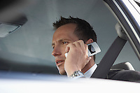 Businessman using mobile phone in car low angle view