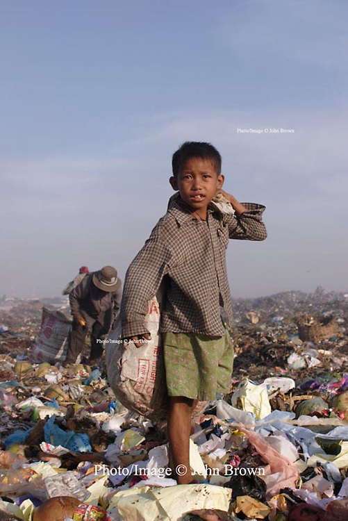 A young worker at the Stung Meanchey Landfill in Phnom Penh, Cambodia, shoulders a bag filled with recyclable material. Over 600 children work at the landfill on a daily basis.