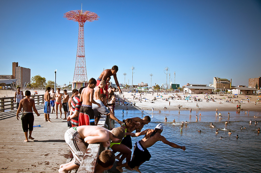 Kids jump in the water from the Coney Island pier in brooklyn, New york, 2010.