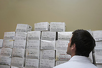 Business man standing in front of stack of filing boxes in storage room back view low angle view