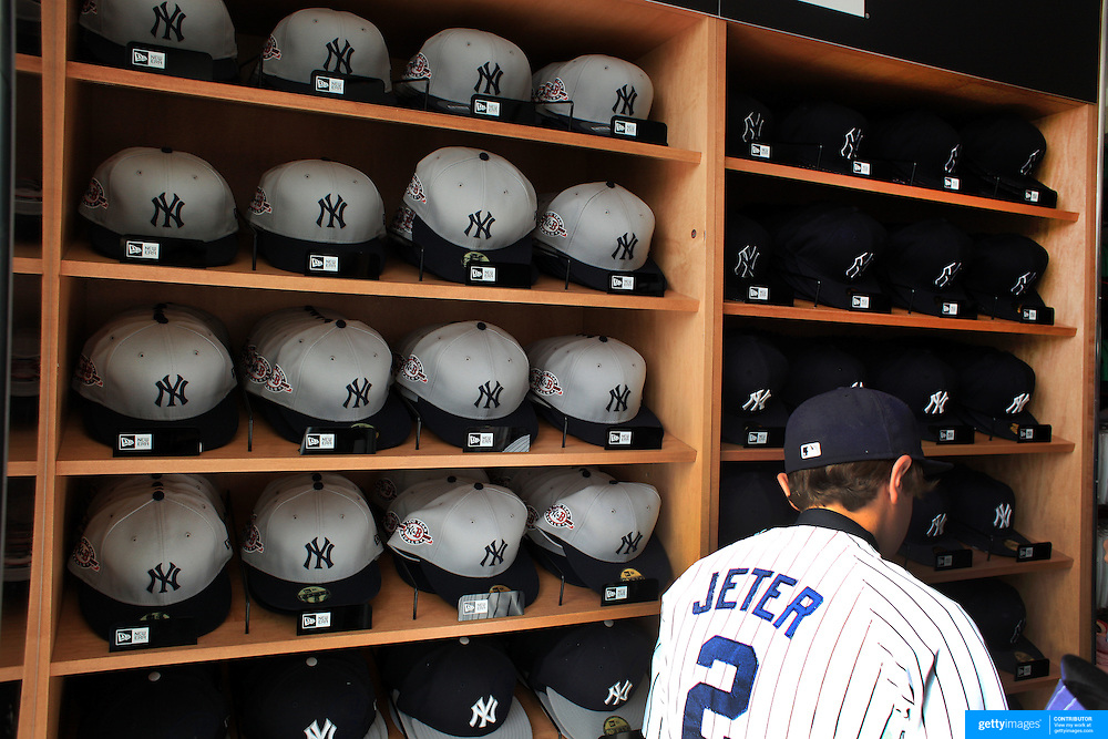 A young fan wearing a Derek Jeter shirt inspects the Yankee baseball hats for sale at the Yankees store at Yankee Stadium, The Bronx, during the New York Yankees V Detroit Tigers Baseball game at Yankee Stadium, The Bronx, New York. 28th April 2012. Photo Tim Clayton