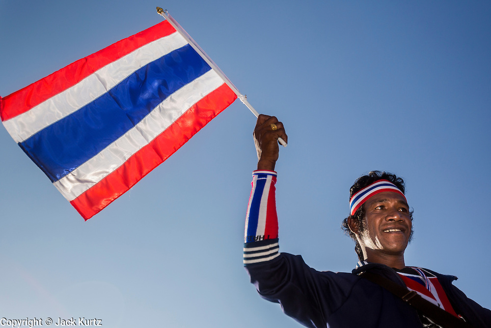 """13 JANUARY 2014 - BANGKOK, THAILAND: An anti-government protestor waves a Thai flag at Victory Monument in Bangkok. Tens of thousands of Thai anti-government protestors took to the streets of Bangkok Monday to shut down the Thai capitol. The protest was called """"Shutdown Bangkok"""" and is expected to last at least a week. The Shutdown Bangkok protest is a continuation of protests that started in early November. There have been shootings almost every night at different protests sites around Bangkok, including two Sunday night, but the protests Monday were peaceful. The malls in Bangkok stayed open Monday but many other businesses closed for the day and mass transit was swamped with both protestors and people who had to use mass transit because the roads were blocked.    PHOTO BY JACK KURTZ"""