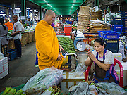 24 FEBRUARY 2016 - BANGKOK, THAILAND: A Buddhist monk prays with a woman who gave him alms in Pak Khlong Talat. Bangkok government officials announced this week that vendors in Pak Khlong Talat, Bangkok's well known flower market, don't have to move out on February 28. City officials are trying to clear Bangkok's congested sidewalks and they've cracked down on sidewalk vendors. Several popular sidewalk markets have been closed in recent months and the sidewalk vendors at the flower market had been told they would be evicted at the end of the month but after meeting with vendors and other stake holders city officials relented and said vendors could remain but under stricter guidelines regarding sales hours. The flower market is one of the best known markets in Bangkok and has become a popular tourist destination.        PHOTO BY JACK KURTZ