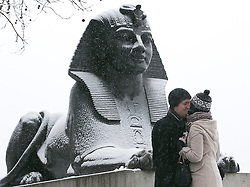 © Licensed to London News Pictures.20_01_2013 LONDON UK.A kissing couple on the Victoria Embankment, with the Sphinx at Cleopatra's Needle .Heavy Snow fall on the third day of  freezing cold weather over most of the country. Photo credit : Andrew Baker/LNP
