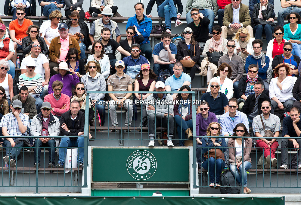 French Open 2015, Feature, Zuschauer sitzen auf der Tribune &uuml;ber einem Eingang mit dem Roland Garros Logo,<br /> <br /> Tennis - French Open 2015 - Grand Slam ITF / ATP / WTA -  Roland Garros - Paris -  - France  - 29 May 2015.