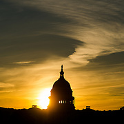 The sun rises behind a silhouette of the dome of the US Capitol Building (Congress) in Washington DC, illuminating the light clouds.
